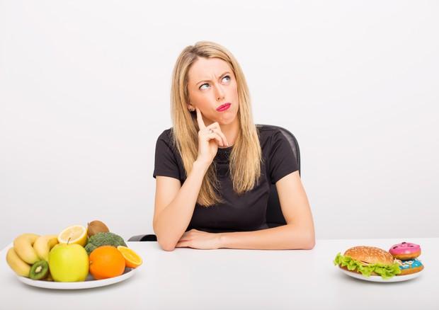 Giovane donna indecisa tra frutta e proteine © Ansa