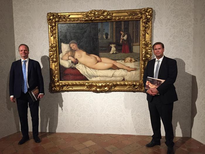 due uomini ben vestiti con delle carte in mano fotografati ai fianchi del dipinto: una donna nuda che si copre ma senza pudore