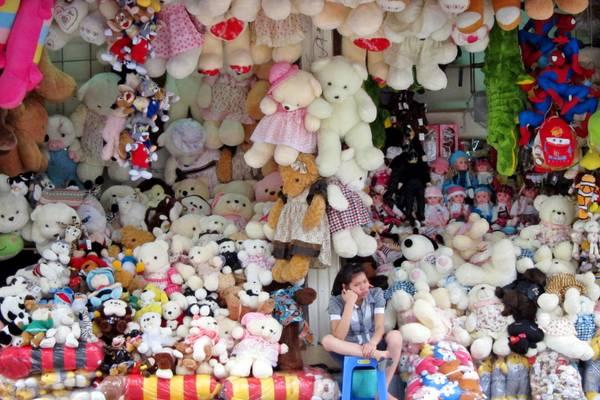 Una giovane ragazza davanti al suo negozio di orsetti di peluche in Vietnam