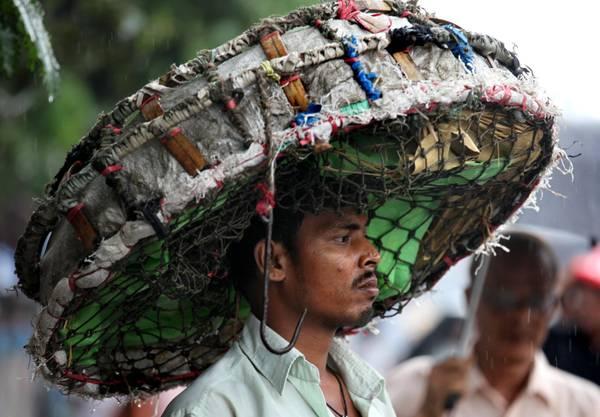 Copricapo anti-pioggia in India per l'arrivo dei monsoni