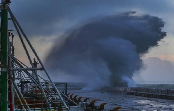 Un'onda si infrange sulla banchina del porto di Kalk Bay a Cape Town, in Sudafrica