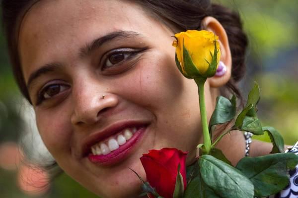 Una ragazza festeggia con i fiori la giornata della non violenza a Kathmandu