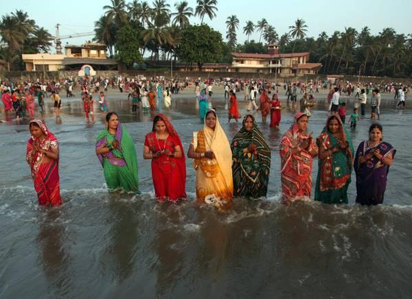 Donne indiane camminano nel Mar Arabico per adorare il sole al tramonto durante le celebrazioni del Chhath Pooja a Mumbai