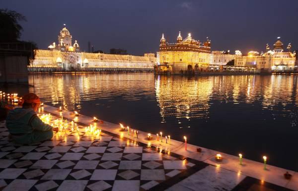 Un bimbo accende candele vicino il Golden Temple di Amritsar, il santuario piu' importante per i Sikh, nel giorno dell'anniversario della nascita del primo Sikh Guru