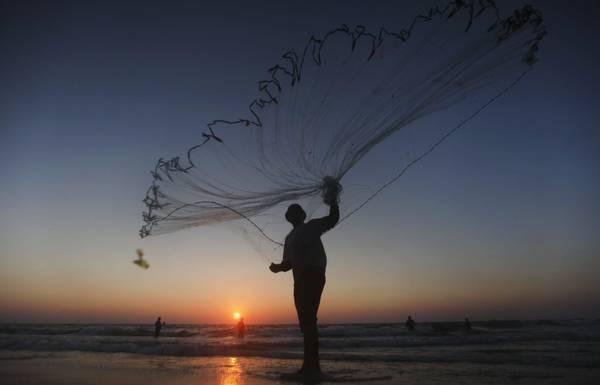 Un pescatore palestinese getta la rete al tramonto sulla spiaggia di Al-Nusirat's