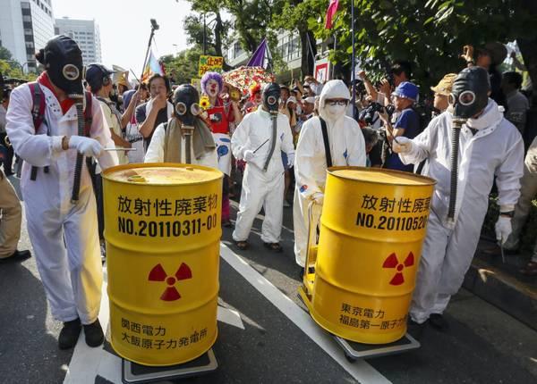 alcuni manifestanti vestiti in tuta bianca e maschere antigas