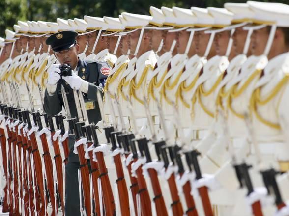 Tokyo, un fotografo delle Forze Armate fa capolino tra gli uomini del picchetto di onore che aspettano il premier Yoshihiko Noda