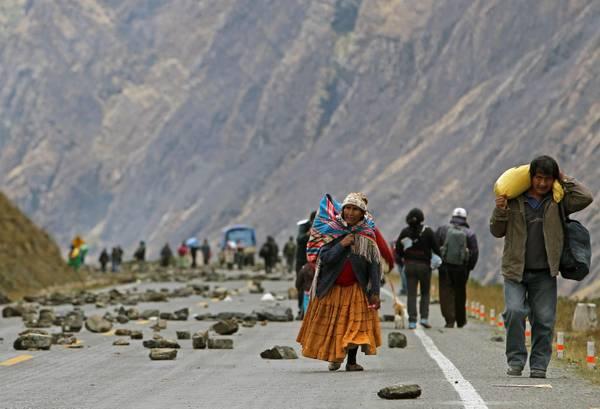 Una donna cammina per una via bloccata da minatori cooperativisti boliviani in localita' Pongo, uno dei accesso a La Paz