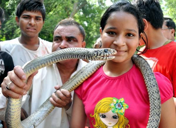 Un bimba tiene in mano un serpente durante la lezione