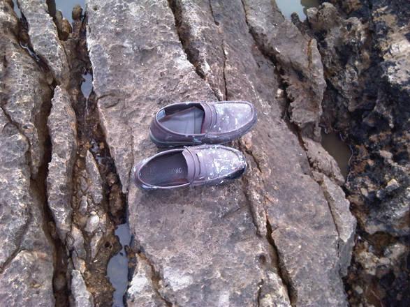 Un paio di scarpe finito tra gli scogli, a seguito del naufragio dell'imbarcazione sulla quale  viaggiavano centinaia di migranti