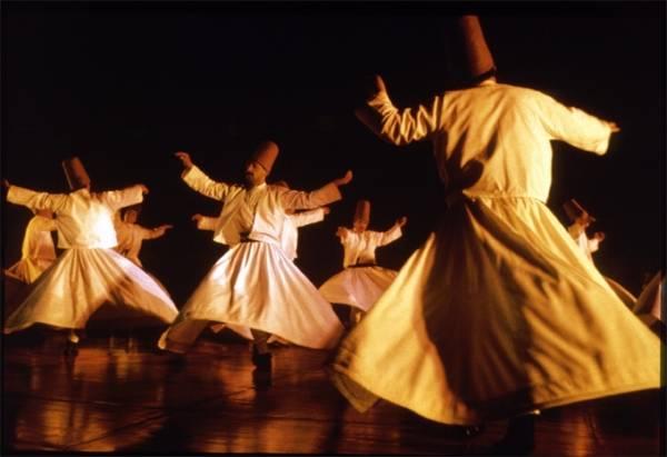 i dervisci, monaci islamici sufi, danzano girando vorticosamente con i loro abiti di lana bianca, le ampie gonne e un cono di feltro rosso in testa