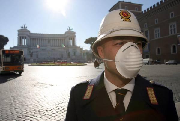 Un vigile urbano in piazza Venezia a Roma con la mascherina per lo smog