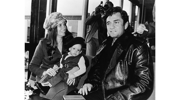 American country singer Johnny Cash (1932 - 2003) sits inside an airport with his wife June Carter Cash (1929 - 2003) and their infant son John Carter Cash, Denmark to begin his Scandinavian tour, circa 1971. (Photo by Express Newspapers/Getty Images)
