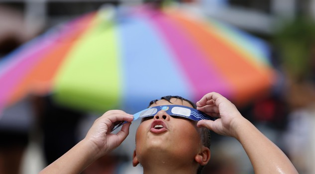 Ezra Packham, of Jacksonville, Fla., looks through his solar glasses in preparation for the solar eclipse Monday, Aug. 21, 2017, on the beach at Isle of Palms,