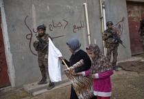 Donne di Mosul alzano la bandiera bianca davanti ai soldati iracheni (ANSA)