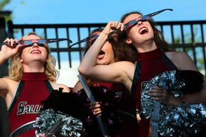 Saluki cheerleaders try out eclipse glasses that they were giving out to visitors to Saluki Stadium on the campus of Southern Illinois University Carbondale, Ill., on Monday, Aug. 21, 2017. (ANSA)