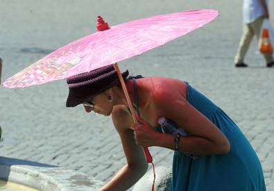 Una ragazza si rinfresca con l'acqua di una fontana (archivio) (ANSA)