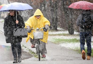 Un uomo in bicicletta sotto la neve a Milano (ANSA)