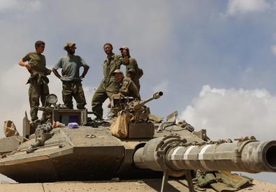 Soldati israeliani sul tetto del loro carro armato in una localita' non specificata della Striscia di Gaza durante la tregua di 7 ore di oggi (ANSA)