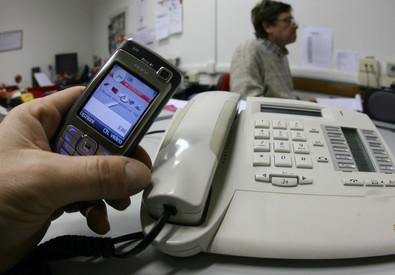 Una persona  tiene in mano un cellulare vicino a un telefono di rete fissa. Foto d'archivio ANSA / FRANCO SILVI (ANSA)