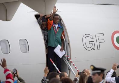 Rifugiati eritrei salgono sull'aereo della Guardia di Finanza (ANSA)