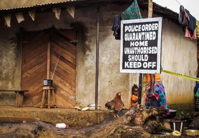 In questa foto d'archivio relativa al 22 ottobre 2014 un bambino si trova vicino a un cartello che avvisa di una casa in quarantena a Port Loko, in Sierra Leone (ANSA)