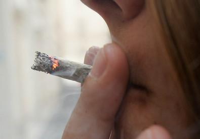 Una ragazza fuma uno spinello (ANSA)