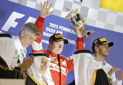 Il pilota finlandese della Ferrari Kimi Raikkonen (centro), secondo classificato, festeggia sul podio del Gran Premio del Bahrain di Formula 1 disputato sul circuito di Sakhir il 19 aprile 2015 (ANSA)