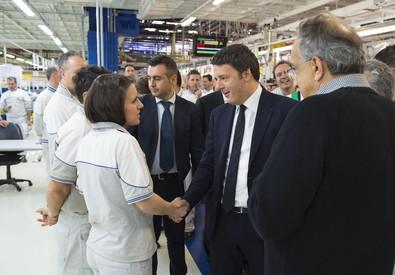 Il presidente del consiglio, Matteo Renzi, saluta gli operai allo stabilimento di Melfi (ANSA)