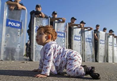 Migranti: baby profuga gattona davanti a agenti con gli scudi (ANSA)