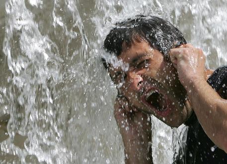 Un uomo cerca refrigerio in una fontana in una foto d'archivio © ANSA
