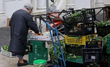 Una anziana cerca del cibo tra gli scarti di un mercato in una foto d'archivio © ANSA