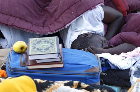 Un migrante dorme accanto al Corano sugli scogli a Ventimiglia © AP
