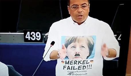 Buonanno con la maglietta 'Merkel  Failed' ha fallito e sopra la scritta il viso della cancelliera tedesca solcato da due baffetti  alla Hitler. © ANSA
