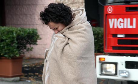 Una vicina commossa dopo l'incendio scoppiato in un appartamento © ANSA