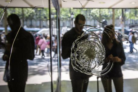 Una vetrina infranta dai colpi esplosi sugli Champs-Elysees © EPA