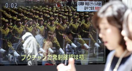 Tokyo, una donna passa davanti a uno schermo tv che mostra le truppe di Pyongyang © AP