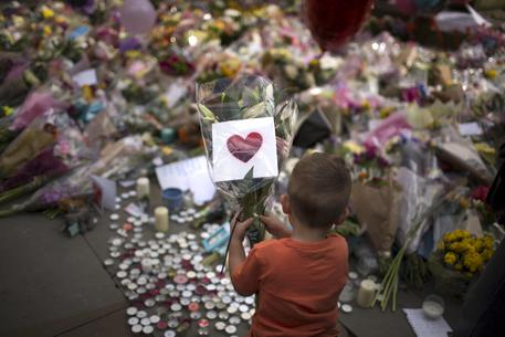 Persone davanti alla piazza della Manchester Arena rendono omaggio alle vittime della strage © AP