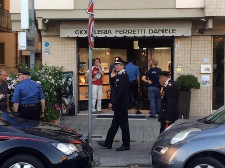 Inquirenti all'esterno della gioielleria dove un uomo morto durante una rapina © ANSA