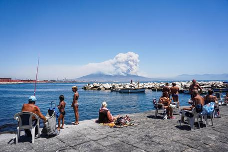 La colonna di fumo scaturita dal vasto incendio che sta mandando in fumo ettari di vegetazione sul Vesuvio, visibile da Napoli, 11 luglio 2017 © ANSA