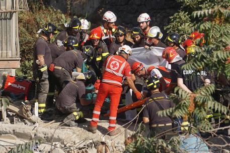 I vigili del fuoco estraggono l'ultimo corpo dalle macerie della palazzina crollata a Torre Annunziata © ANSA