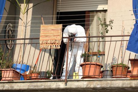 La polizia scientifica lavora sul balcone dell'appartamento dove una donna di 46 anni ed un bambino  sono stati uccisi dal marito 51enne di lei a colpi di mannaia a Cremona © ANSA