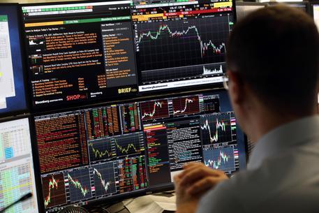 Un operatore di Borsa di una banca davanti ai monitor
