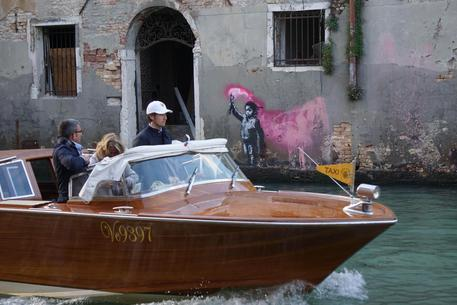A motorboat passes in front of the alleged work of the American street artist Bansky, just called