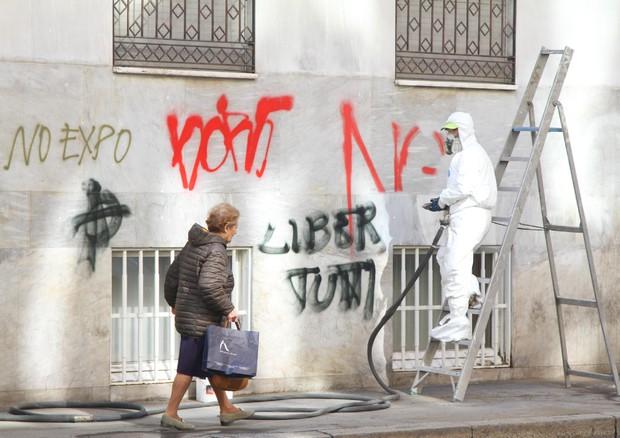 Personale dell'Amsa e cittadini volontari ripuliscono i muri di Milano e riparano i danni dopo gli scontri avvenuti nel giorno dell'inaugurazione dell'Expo (ANSA)