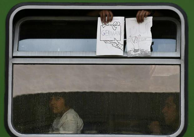 Migranti mostrano il biglietto del treno a Budapest (ANSA)