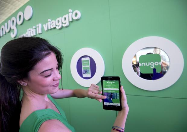 Una ragazza mostra l'app di Nugo all'esterno dell'istallazione Nugo Space Experience presso la  stazione Termini di Roma © ANSA