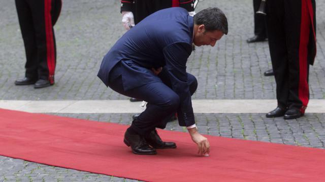 Renzi raccoglie una piuma nel cortile di Palazzo Chigi