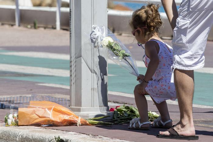 Una bambina posa dei fiori dove ieri sera ha avuto luogo la mattanza.