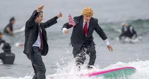Gary Crane, left, of Long Beach cheers on Dave Granoff, of Newport Beach, who dressed as a flag-waving President Donald Trump as they surf with approximately 100 other surfers wearing wacky Halloween costumes on Saturday, Oct. 28, 2017